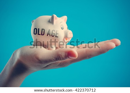 Piggy bank in a human hand with inscription OLD AGE on a blue background - stock photo