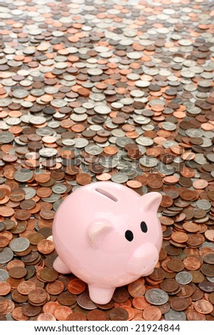 Piggy bank in a sea of coins - stock photo