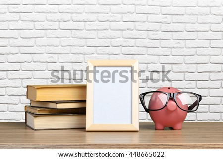 Piggy bank in glasses with books - stock photo
