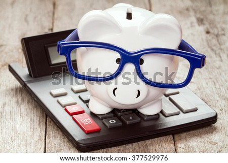 Piggy bank in glasses with calculator on the wooden background