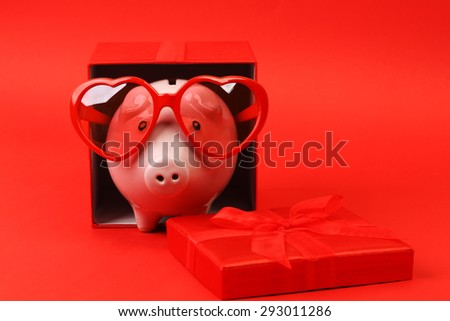 Piggy bank in love with red heart sunglasses standing in gift box with ribbon on red background - horizontal - stock photo