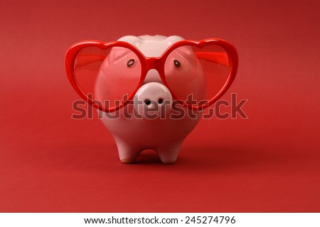 Piggy bank in love with red heart sunglasses standing on red background - stock photo