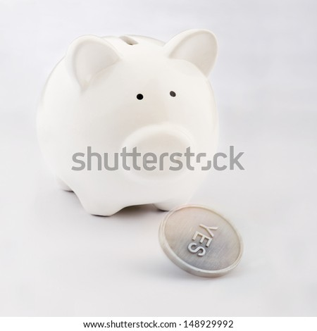 Piggy bank looking to a flipping coin - stock photo