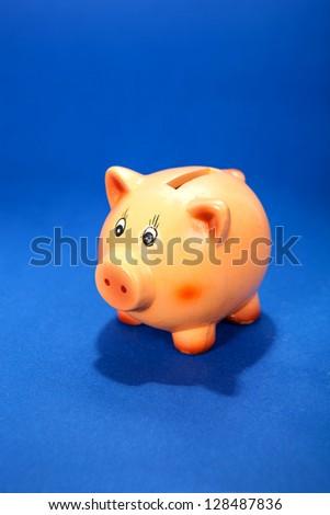 Piggy bank on blue background - stock photo