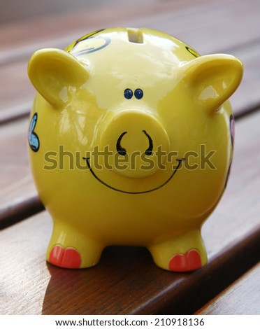Piggy bank on brown table; - stock photo