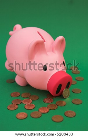 Piggy bank on green amongst scattered pennies - shallow dof - stock photo