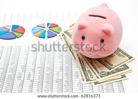 Piggy bank on money with business charts - stock photo
