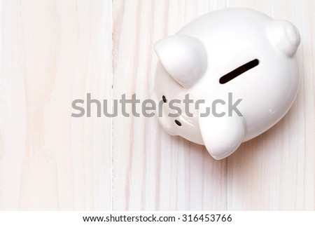 Piggy bank on the white wooden background, top view - stock photo