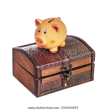 Piggy bank on top of a closed chest isolated on white