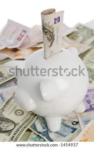 piggy bank on top of a pile of assorted world notes - stock photo