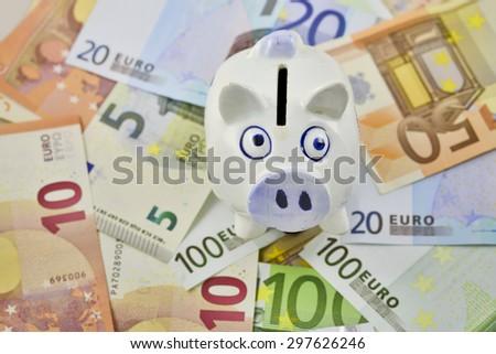Piggy Bank On Top of Euros - stock photo