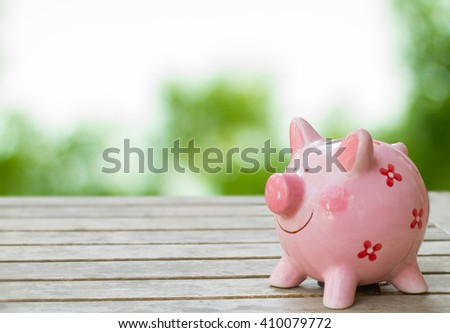 Piggy bank on wood table top over blur nature background