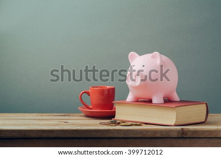 Piggy bank on wooden table with coffee cup and book. Saving money, budget planning concept. - stock photo
