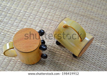 piggy bank or money box made of bamboo wood on woven dried sedge mat - stock photo