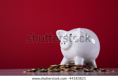 Piggy bank over a lot of coins with a red background