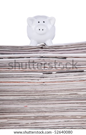 Piggy bank over a stack of newspaper (selective focus) - stock photo
