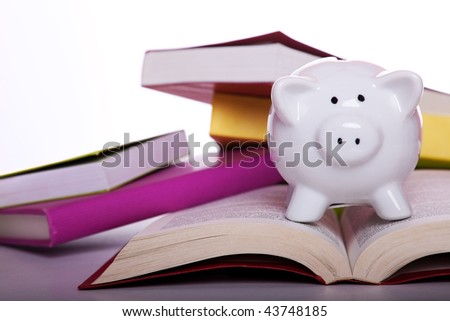 piggy bank over some colorful books (isolated on white)