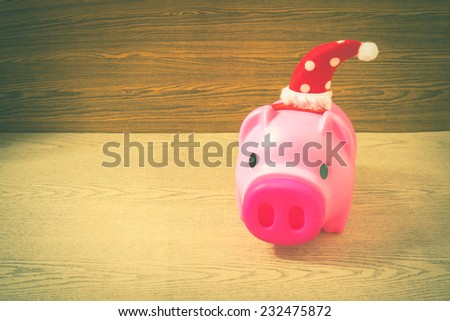 piggy bank ready for Christmas holiday on wooden background vintage color tone  , saving and financial concept.  - stock photo
