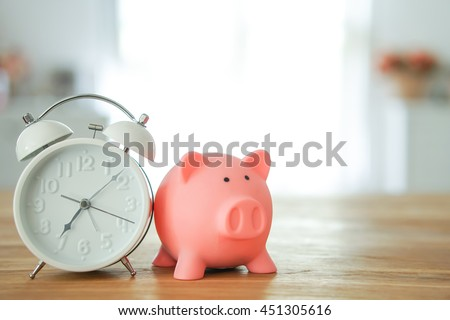 Piggy bank save coin and alarm clock, time and money concept. copy space on right side. - stock photo