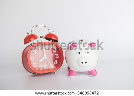 Piggy bank save coin and red alarm clock, time and money concept.