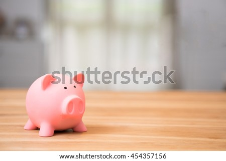 piggy bank save coin on wooden desk, copy space on Right side. - stock photo
