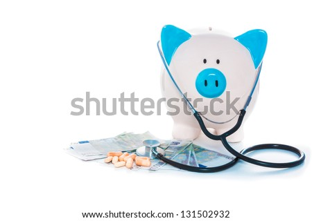 Piggy bank sitting on pile of dollars with stethoscope and pills on white background - stock photo