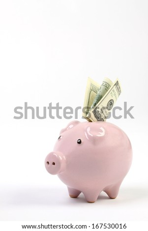 Piggy bank style money box with one hundred dollars falling into slot on a white studio background  - stock photo