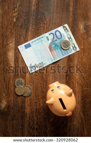 Piggy bank, twenty euro note and eurocent coins on brown wooden background. View from top. - stock photo
