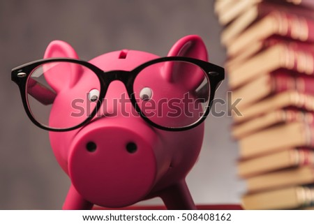 piggy bank weaking glasses and faces the camera - closeup picture near pile of books