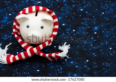 Piggy bank wearing a scarf on star background, Christmas savings