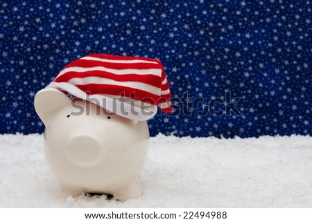Piggy bank wearing Christmas stocking cap sitting on snow with star background, Christmas savings