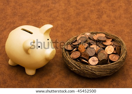 Piggy bank with a bowl of pennies on a brown textured background, seeing your savings - stock photo