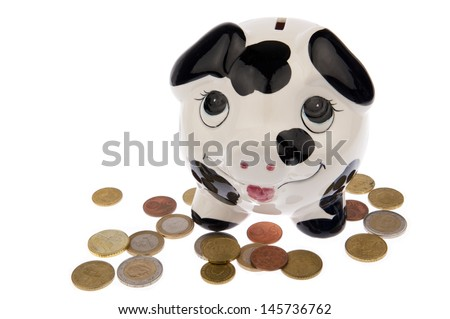 Piggy bank with black and white cow spots, looking upwards and standing in a variety of Euro coins, isolated in white background - stock photo