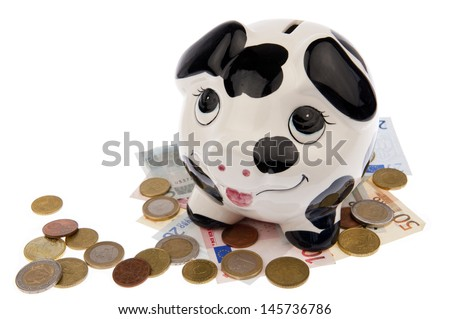 Piggy bank with black and white cow spots, looking upwards and standing on a variety of Euro banknotes and coins, isolated in white background - stock photo