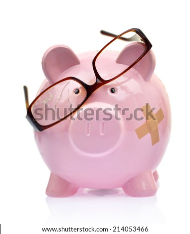 Piggy bank with broken eyeglasses and bandage - stock photo