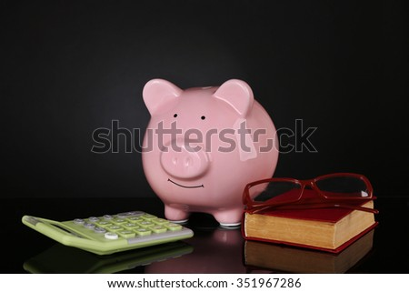 Piggy bank with calculator, book and glasses on dark background - stock photo