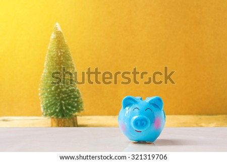 piggy bank with Christmas tree background., abstract background to time to start to saving or solution for keep money for celebration. - stock photo
