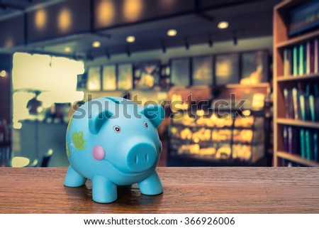piggy bank with coffeeshop or bakery shop background, abstract background to time to start to saving or solution for keep money for investment - stock photo