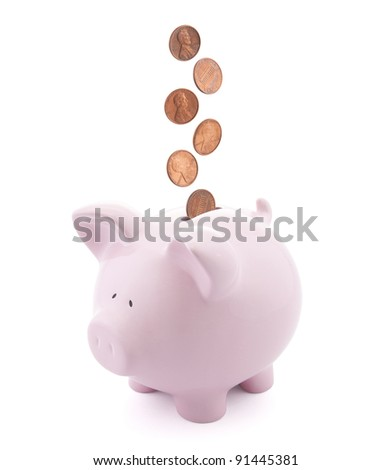 Piggy bank with coins falling into slot - stock photo