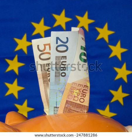 Piggy bank with euro notes, EU flag in the background - stock photo