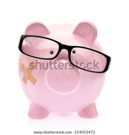 Piggy bank with eyeglasses and bandage - stock photo