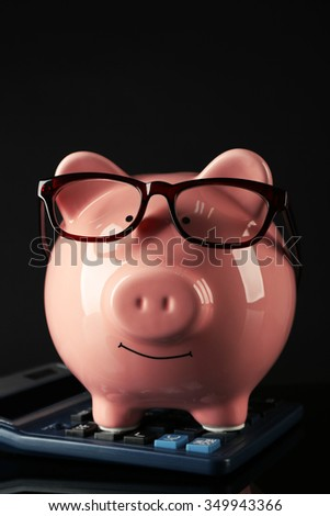Piggy bank with glasses and calculator on a black background - stock photo