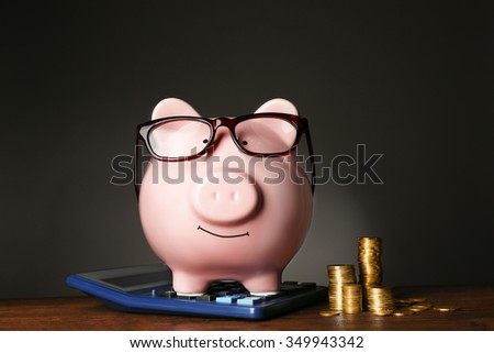 Piggy bank with glasses,coins  and calculator on table , gray background - stock photo