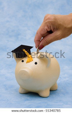 Piggy bank with graduation cap on a blue background, education savings - stock photo