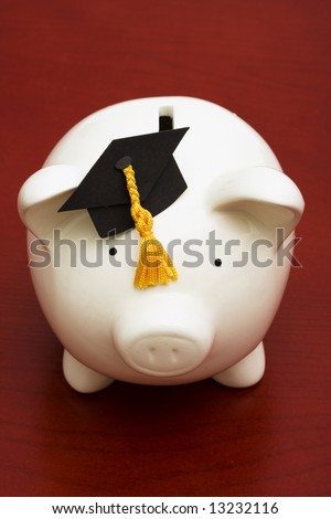 Piggy bank with graduation cap – the cost of education - stock photo