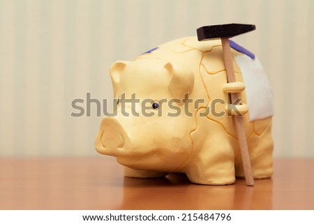 piggy bank with hammer, vintage look. - stock photo