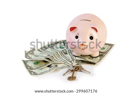 Piggy bank with house keys  and money isolated on white - stock photo
