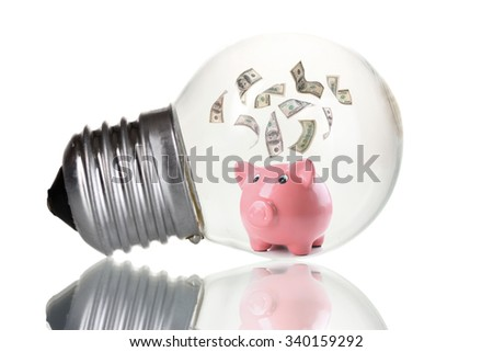 Piggy bank with money inside light bulb, isolated on white - stock photo