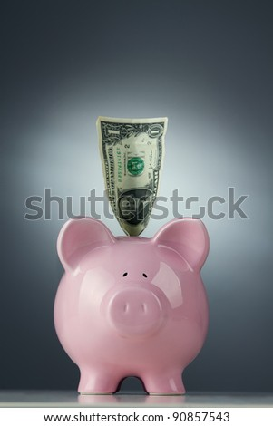 Piggy bank with one dollar bill - stock photo