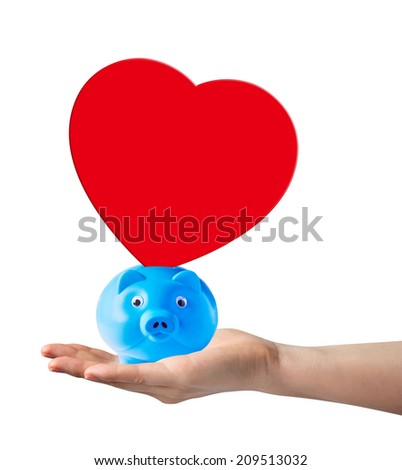 Piggy bank with red paper shape heart on hand - stock photo